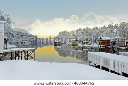 Scenic lake in the winter,early morning colors and snow on the boathouses and shore.