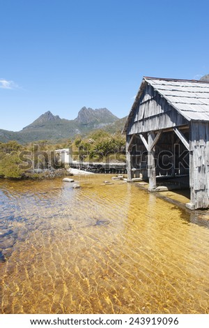 Scenic landscape of Cradle Mountain National Park in Tasmania, Australia, with Dove Lake and historic boat shed, blue sky as copy space. - stock photo