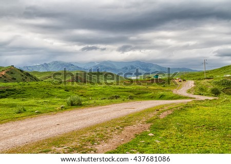 Scenic landscape of green grasslands in Kyrgyzstan, Central Asia - stock photo