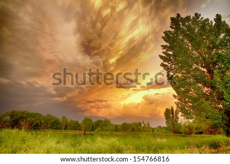 Scenic landscape view at Pella Ponds in Boulder County Colorado with an apocalyptic sunset colorful angry sky.   - stock photo