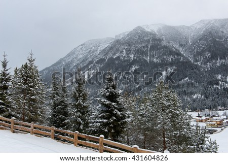 Scenic landscape view from above past snow-covered pine trees of the alpine ski resort of Achenkirch in the Austrian alps nestling in a snowy valley below mountain peaks enveloped in cloud or mist - stock photo