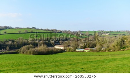 Scenic Landscape View of a Lush Green Field with a Beautiful Blue Sky Above - stock photo