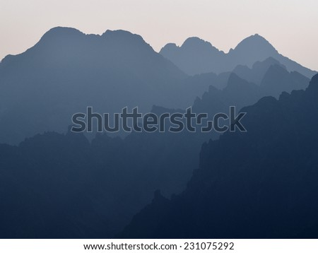 Scenic layers of the high mountains in the early morning - stock photo