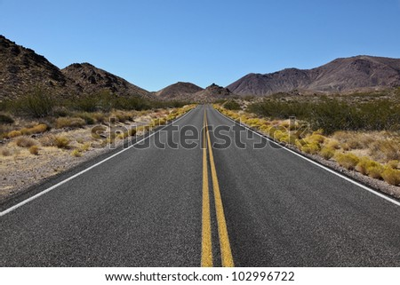 Scenic long straight desert highway ahead of Death Valley National Park, California - stock photo