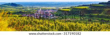 Scenic mountain panorama with vineyards and old picturesque town in Germany at sunset, Black forest, Kaiserstuhl, Oberrotweil.Travel and wine-making background.