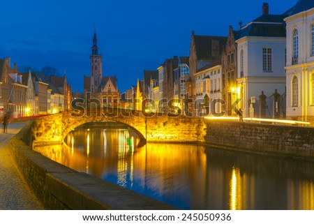 Scenic night cityscape with views of Spiegelrei, Canal Spiegel, bridge and church in Bruges, Belgium - stock photo