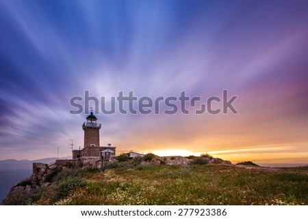 Scenic old lighthouse near Perachora, Greece against a cloudy sky, long exposure photography - stock photo