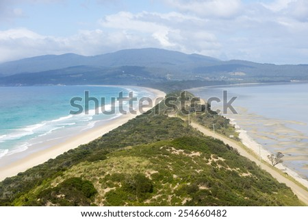 Scenic panorama lookout The Neck beach on Bruny Island, Tasmania, Australia, with wide bay of southern ocean, mountains blurred background, copy space blue sky. - stock photo