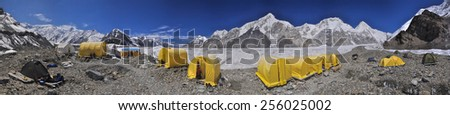 Scenic panorama of tents on Engilchek glacier in picturesque Tian Shan mountain range in Kyrgyzstan - stock photo