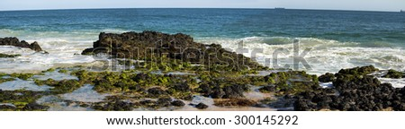 Scenic panorama of  the Indian Ocean waves breaking on grey weathered  basalt rocks at  Ocean Beach Bunbury Western Australia on a fine sunny  afternoon in  mid winter . - stock photo