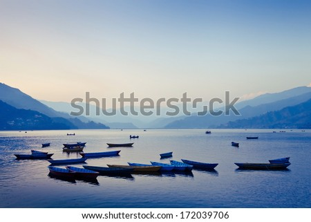 scenic panoramic view of boat on the lake by sunset, Nepal, Pokhara - stock photo