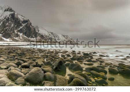 Scenic pebble beach in Eggum, Lofoten Islands, Arctic, Norway, Scandinavia, Europe on a cloudy, winter day. - stock photo