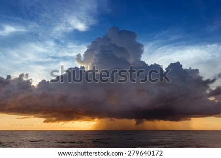 Scenic photo of beautiful sea sunset with yellow and blue sky and rain clouds - stock photo