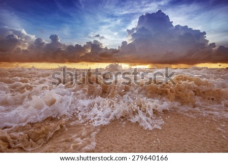 Scenic photo of beautiful sea sunset with yellow and blue sky, rain clouds  and tidal bore  - stock photo