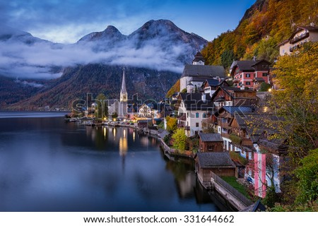 Scenic picture-postcard view of famous historic Hallstatt mountain village with Hallstatter See in the Austrian Alps in twilight during blue hour at dawn in fall, region of Salzkammergut, Austria - stock photo