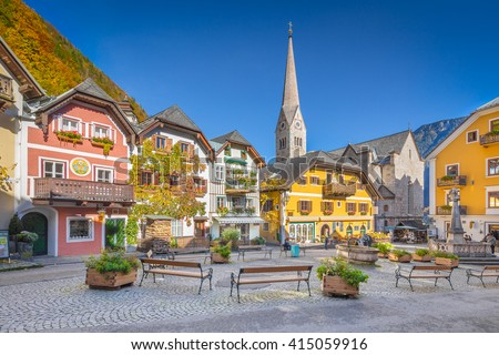 Scenic picture-postcard view of the historic town square of Hallstatt with traditional colorful houses and church at Hallstatter See in the Austrian Alps in fall, region of Salzkammergut, Austria - stock photo
