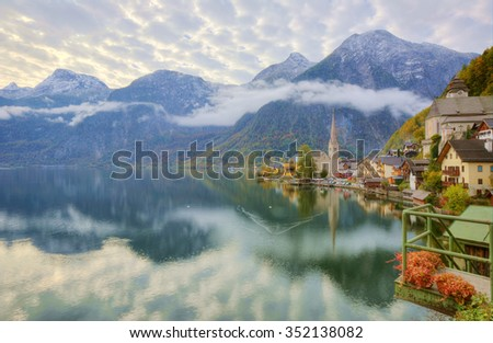Scenic postcard view of famous Hallstatt, a peaceful village by Hallstaetter Lake in Austrian Alps ~ Morning lake scenery with reflections of mountains, village and beautiful sky on smooth water  - stock photo