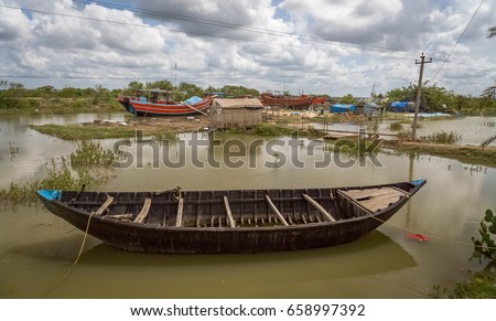Scenic rural landscape view of a fishing village with wooden fishing boats and trawlers on water at the inland tidal creek at Digha Mohona West Bengal, India.