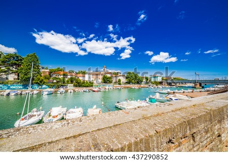 Scenic spring view of pier with ancient and modern buildings, ships, yachts and other boats in Rimini, Italy