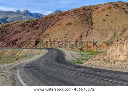 Scenic summer view with the bend of the asphalt road in the mountains of red stone on a background of blue sky and clouds on a sunny day