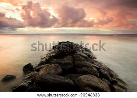 scenic sunrise in Kauai, Hawaii with rocky breakwater surrounded by silky sea water due to long exposure - stock photo