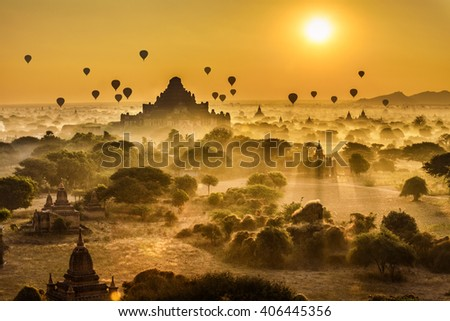 Scenic sunrise with many hot air balloons above Bagan in Myanmar. Bagan is an ancient city with thousands of historic buddhist temples and stupas. - stock photo