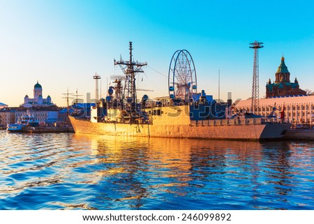 Scenic sunset evening view of the Old Town harbor port with docked military ship in Helsinki, Finland - stock photo