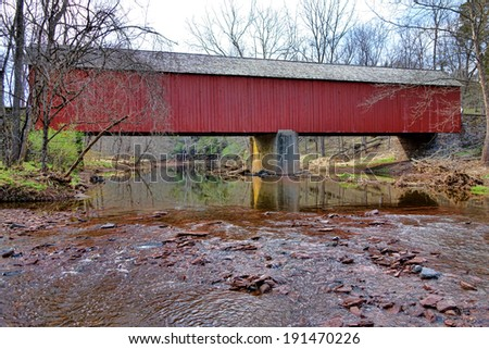 Scenic Tinicum Creek flowing under the Frankenfield covered bridge historic crossing span over the in Bucks County Pennsylvania  - stock photo