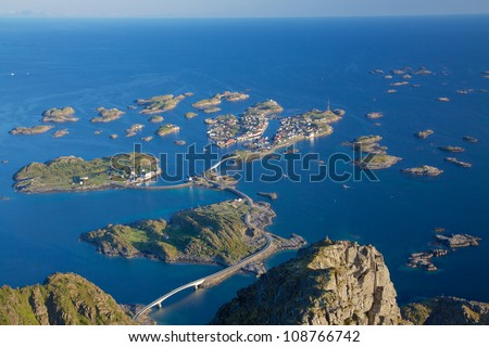 Scenic town of Henningsvaer on Lofoten islands in Norway with large fishing harbour and bridges connecting rocky islands - stock photo
