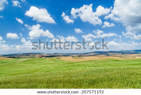 Scenic Tuscany landscape with rolling hills and beautiful cloudscape in Val d'Orcia, Italy - stock photo