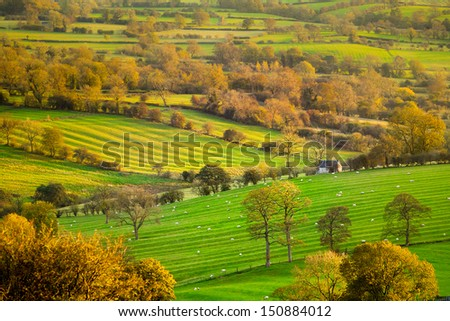 Scenic view across farmland at sunset in the Derbyshire Dales, England, UK - stock photo