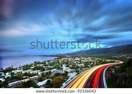 Scenic view Bay of Saint Paul with colorful slow motion effect traffic lights on highway in foreground, Reunion Island. - stock photo