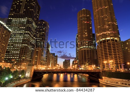 Scenic view from a Chicago River bridge after sunset.  Historic skyscrapers along the River with a deep blue sky in downtown Chicago. - stock photo