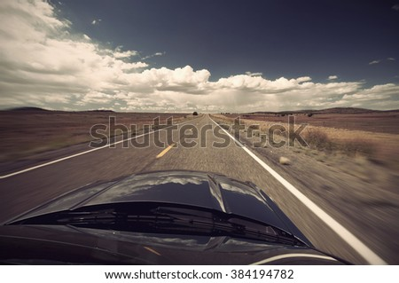 scenic view from car on long lonely old asphalt road Route 66 and blue sky, USA, Vintage filtered style - stock photo