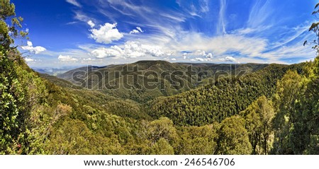 Scenic view from Devil's hole lookout at Barrington Tops National park towards woods covered mountain range and underlying valley on sunny summer day  - stock photo