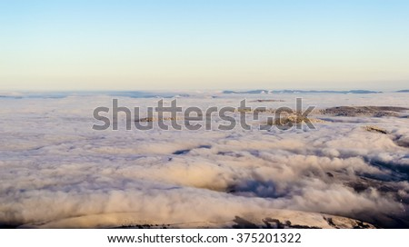 Scenic view, from the mountain top, of the clouds in the valleys. The sky is clear. Evening sunlight falling on the clouds. Some peaks are seen on the horizon. Winter. Carpathian Ukraine - stock photo