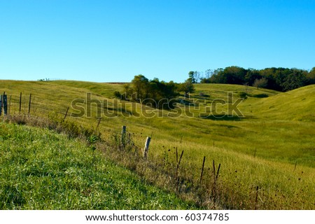 Scenic view of a beautiful pasture in Iowa with blue sky and fence line