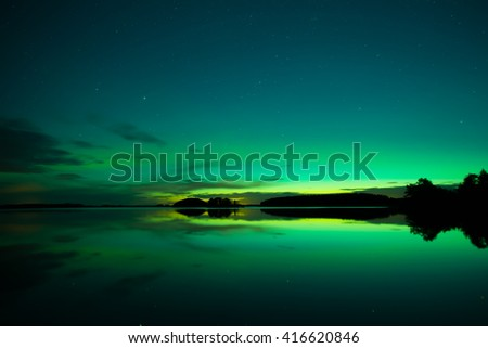 Scenic view of a calm lake with northern lights - stock photo