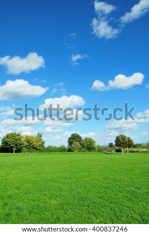 Scenic View of a Lush Green Field with a Beautiful Blue Cloudy Sky Above - stock photo