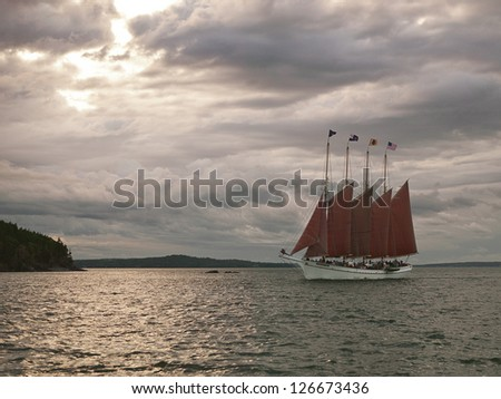 Scenic view of a sailboat in sea with cloudy sky in background.