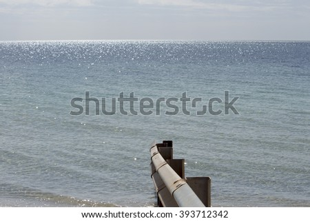 Scenic view of a steel fence at  Forrest Beach near Busselton Western Australia on a cloudy afternoon in autumn is calm and remote.