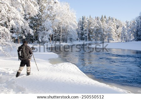 Scenic view of a sunlight river in winter with a photographer - stock photo