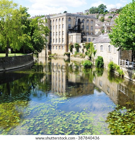 Scenic View of an Apartment Building Reflected in the River of a Picturesque Town - Namely the Landmark Bradford on Avon in Wiltshire England - stock photo
