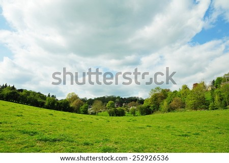 Scenic View of an Open Farmland Field with a Dramatic Cloudy Sky above in Wiltshire England - stock photo
