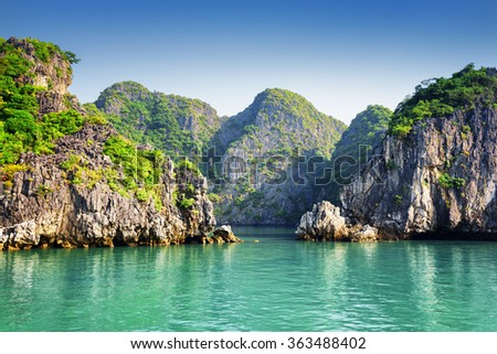Scenic view of azure water and karst islands on blue sky background in the Ha Long Bay at the Gulf of Tonkin of the South China Sea, Vietnam. The Halong Bay is a popular tourist destination of Asia. - stock photo