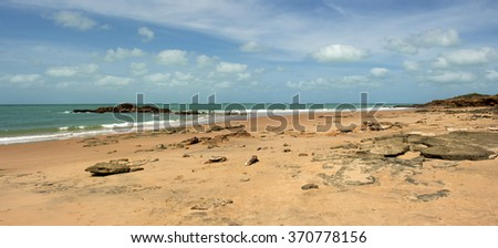 Scenic view of   beautiful remote Reddell Beach,  in tropical  Broome, North Western Australia on a cloudy morning in the summer Wet Season with ancient rocks   strewn on the sandy shore.