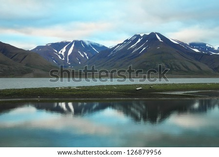 Scenic view of black rocks with melting snow and colorful dramatic sky reflected in calm water of Advent Bay near Longyearbyen, Norway, Spitsbergen archipelago (Svalbard island), Norway, Greenland sea - stock photo