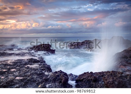 Scenic view of blowhole on rocky coastline with sunset cloudscape background, Reunion Island. - stock photo