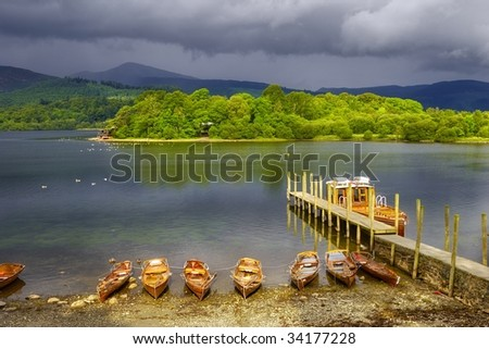 Scenic view of boats moored by wooden pier on Derwent Water, Lake District National Park, Cumbria, England. - stock photo