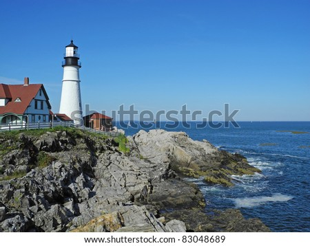 Scenic view of boulders, cliffs and sky, and Portland Head Light at Fort Williams, in beautiful Portland, Maine.